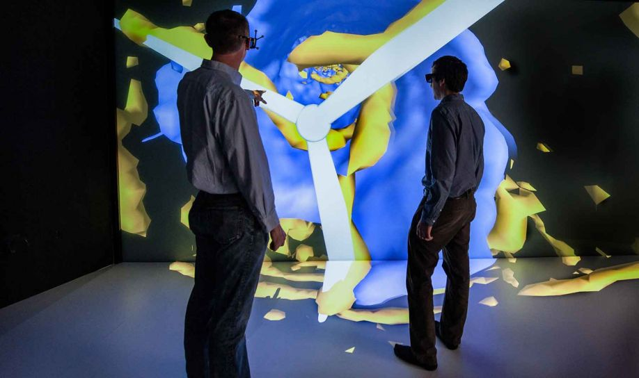 An engineer wearing special glasses points to an image on a large visualization as another engineer looks on.