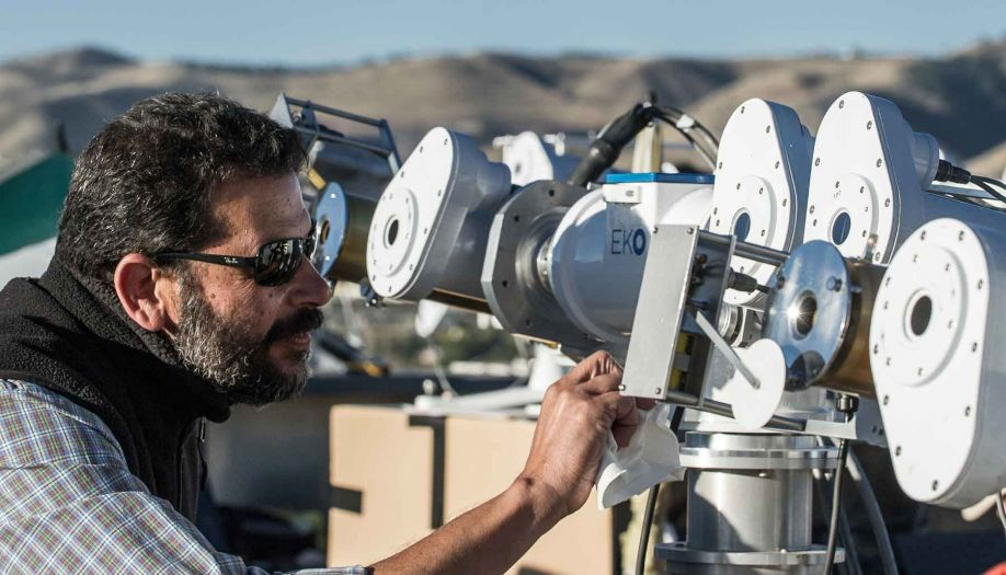 A man works with solar radiation instruments outdoors.