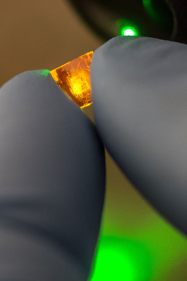 A square of perovskite crystal luminesces from a light being directed at in an NREL laboratory.